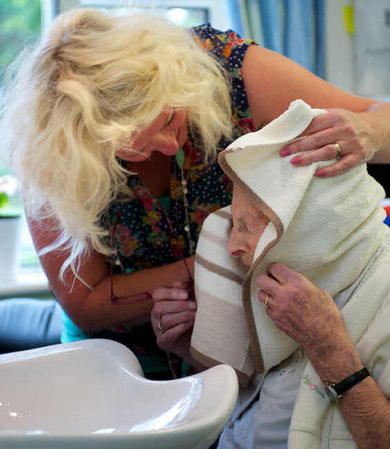 Caremark Domiciliary Care worker washing hair