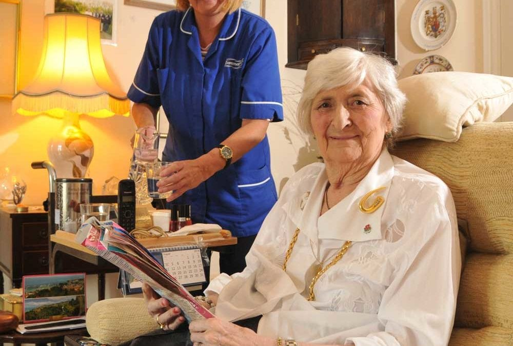 Elderly woman smiling at camera as care assistant pours drink